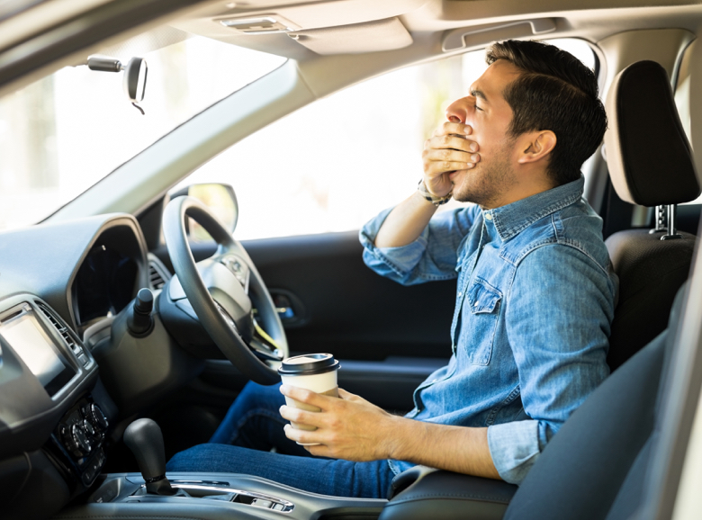 Man yawning at steering wheel