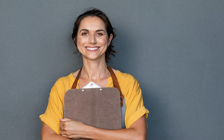 smiling worker wearing an apron and holding a clipboard