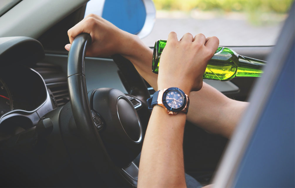 Person driving with a drink in their hand